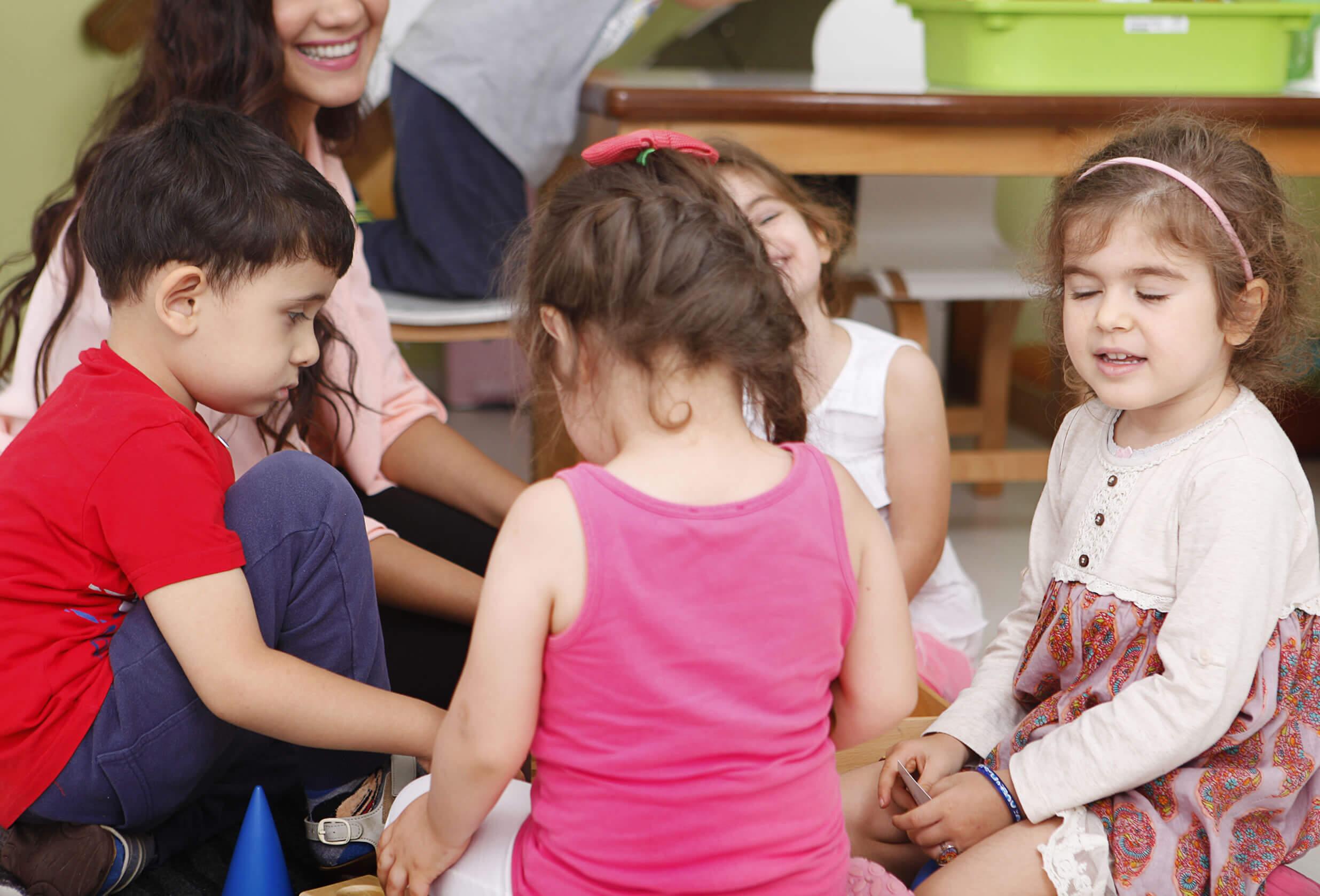 Kinder spielen unter Aufsicht einer Erzieherin