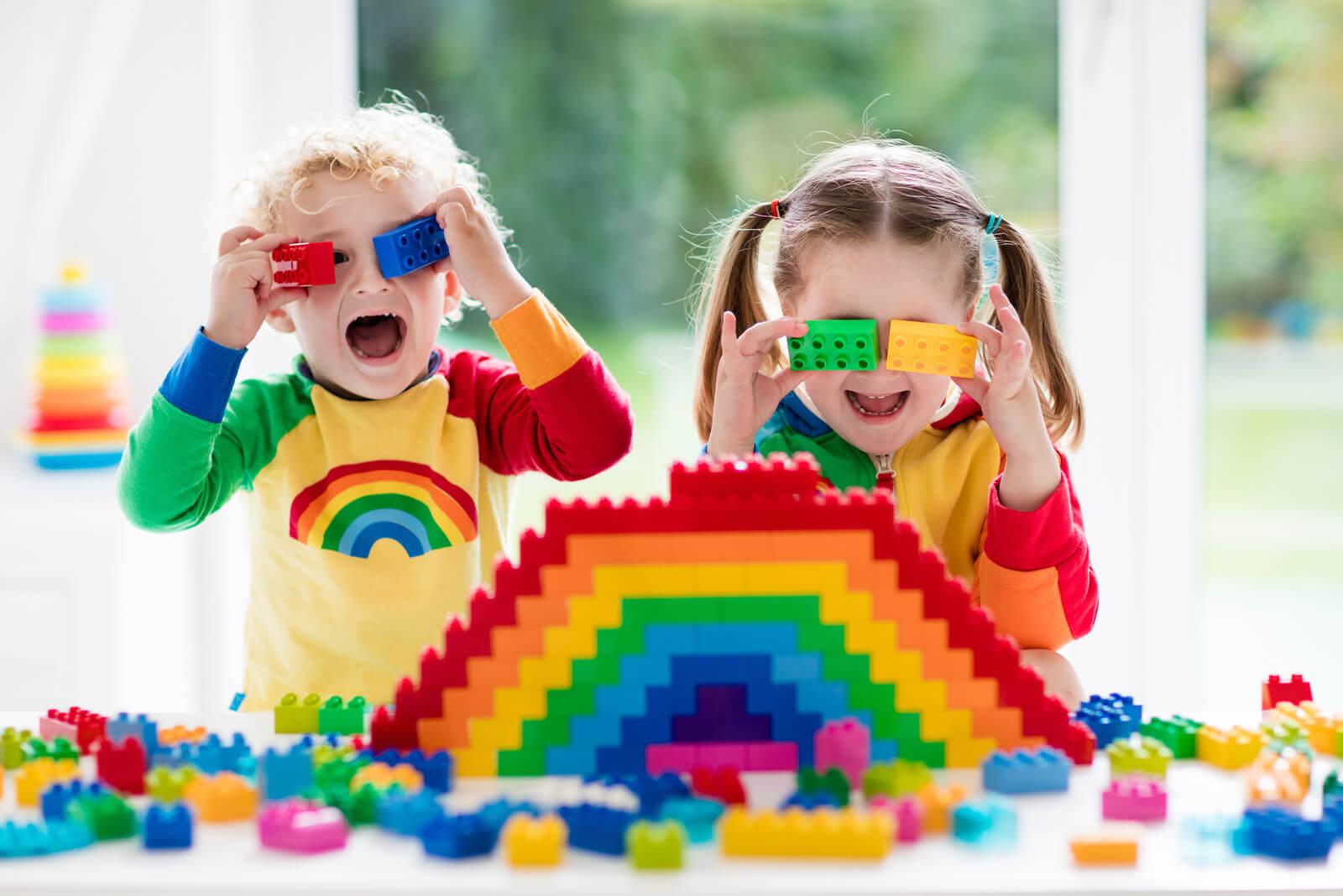 Zwei Kinder spielen mit bunten Bausteinen