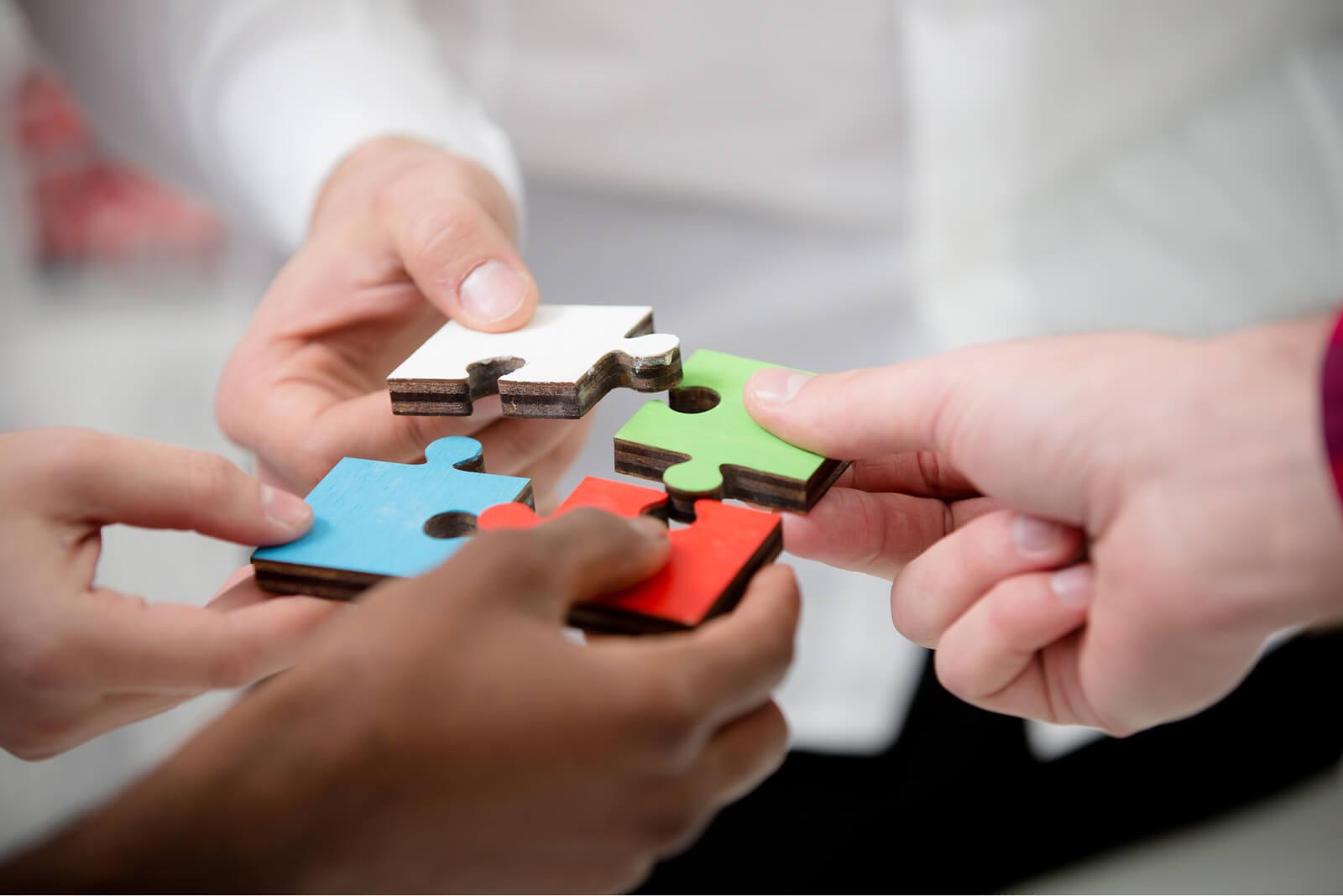 Vier Personen formn ein Puzzle