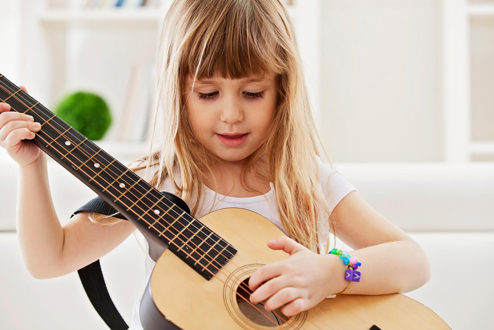Kleines Mädchen spielt auf der Gitarre