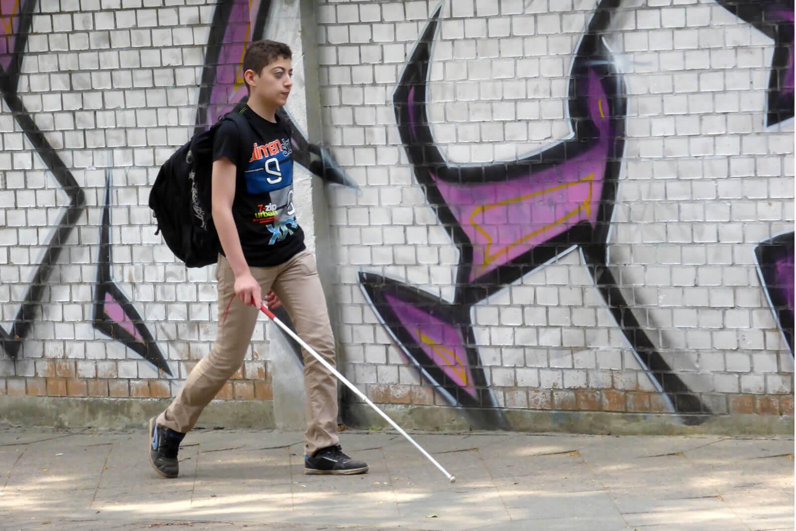 Junge mit Blindenstock überquert Zebrastreifen