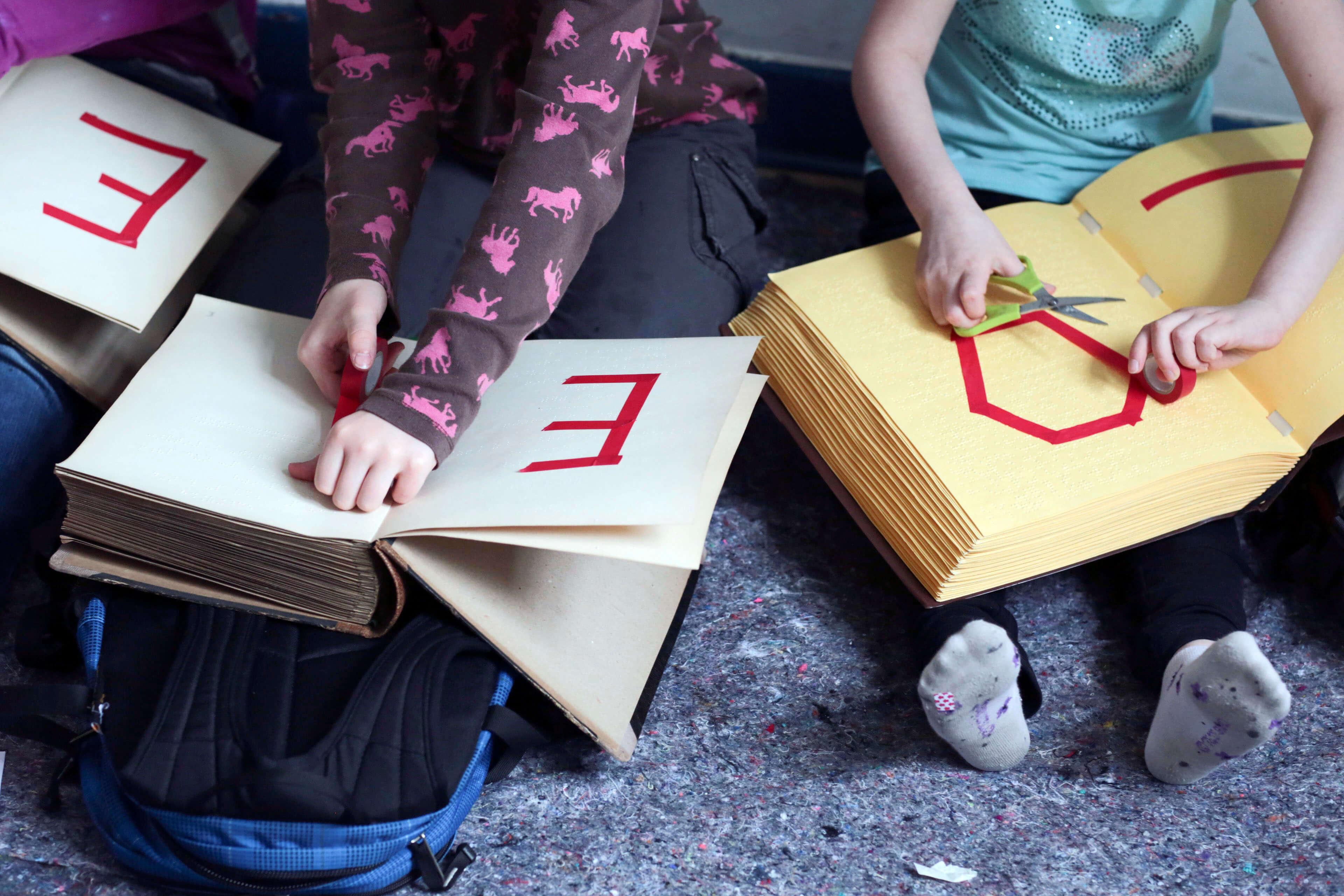 Kinder kleben Buchstaben in Bücher