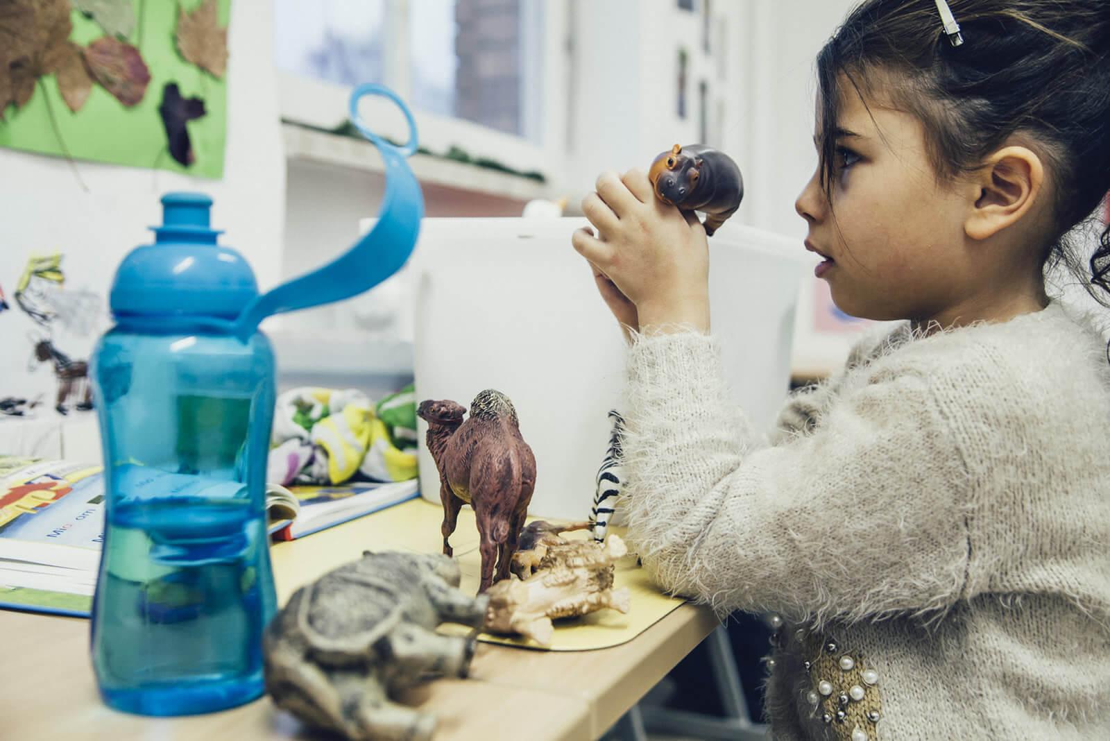 Mädchen beim Spielen mit Tieren aus Plastik